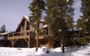 Large log cabin nestled in the snow surrounded by fir trees
