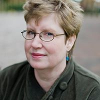 Helena Dixon a woman with short dark blonde hair and glasses.