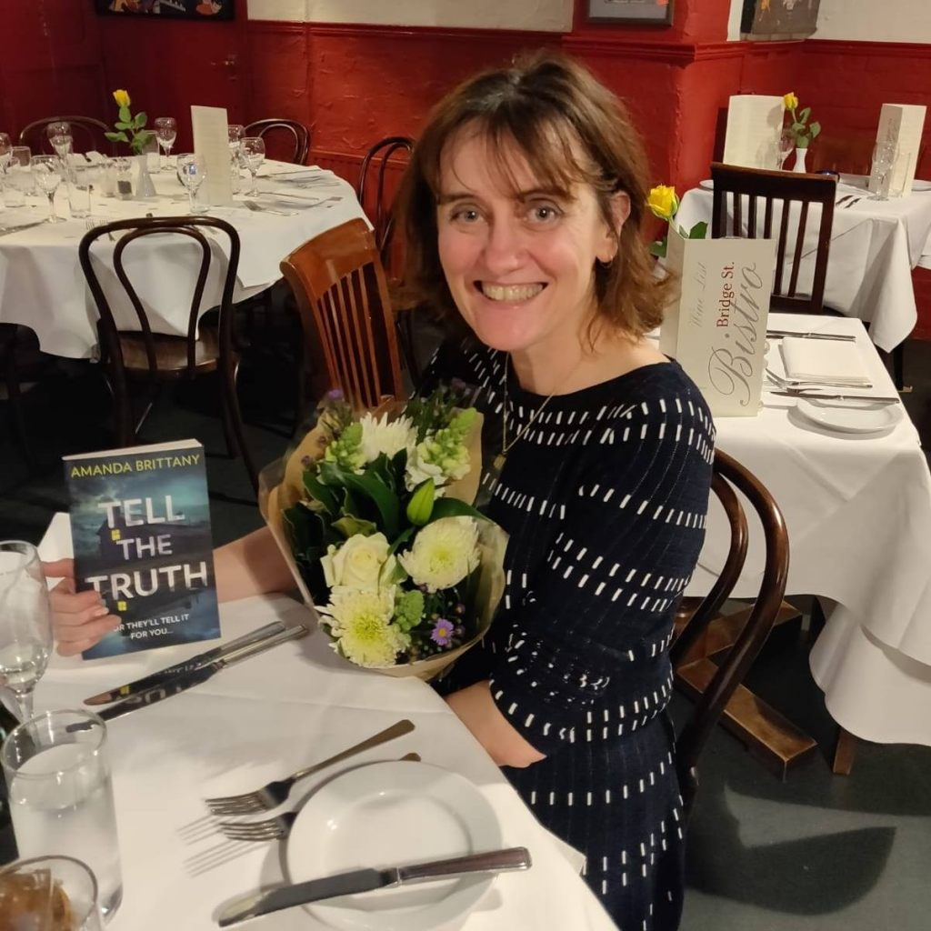 Author Amanda Brittany - Smiling middle aged woman with shoulder length brown hair wearing a black dress and seated at a table in a restaurant with a bunch of flowers and a copy of the book
