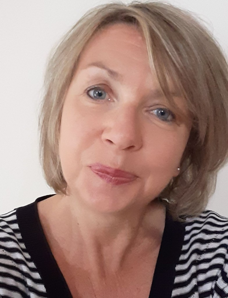 Author photo, a middle aged woman with shoulder length blonde hair and blue eyes.