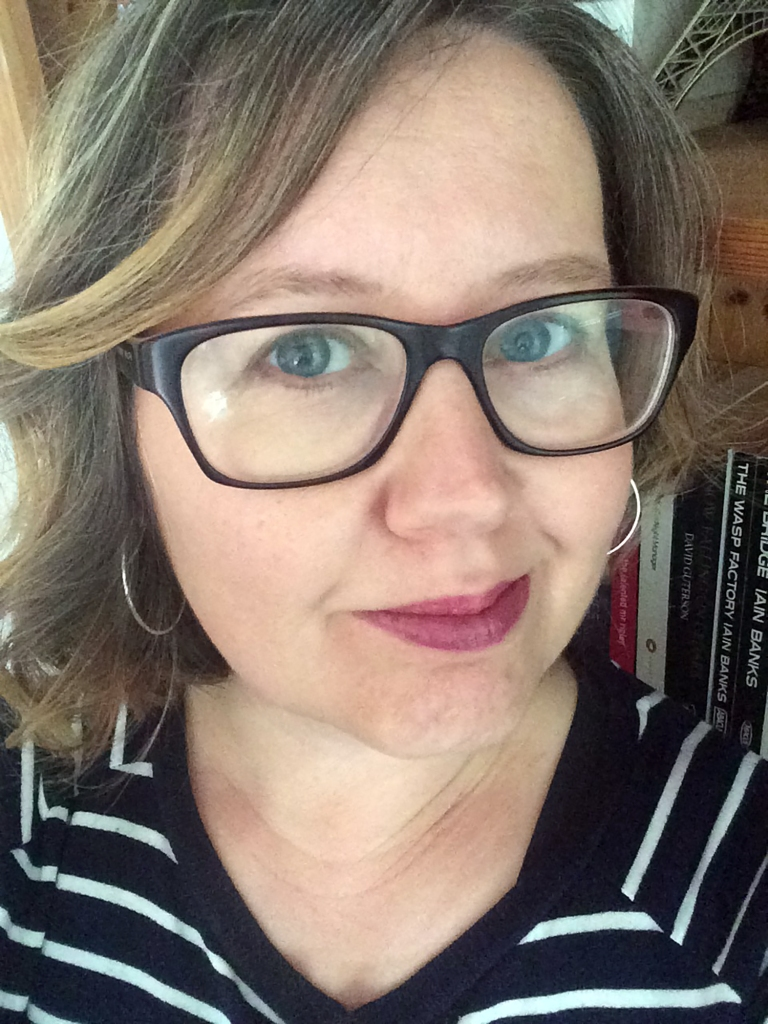 Author Fiona Leitch. A middle-aged blonde woman with shoulder length hair and dark rimmed glasses and a pink-lipsticked smile.