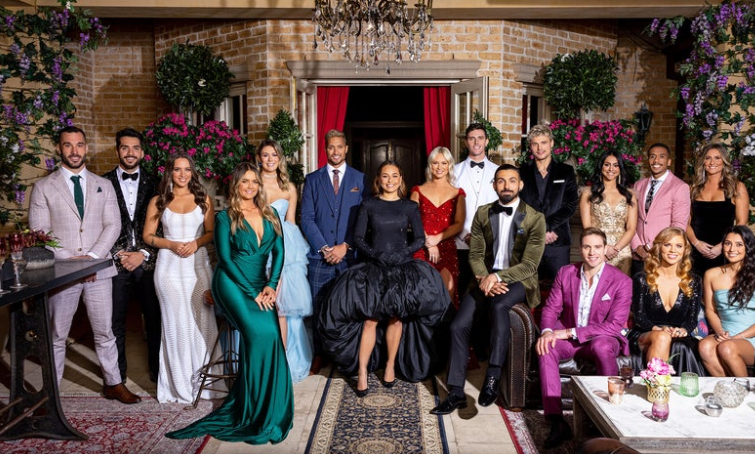 Cast of The Bachelorette - 8 women and 8 men vying for Brooke, who is a 26-year old Indigenous woman centre of group, wearing a black gown.