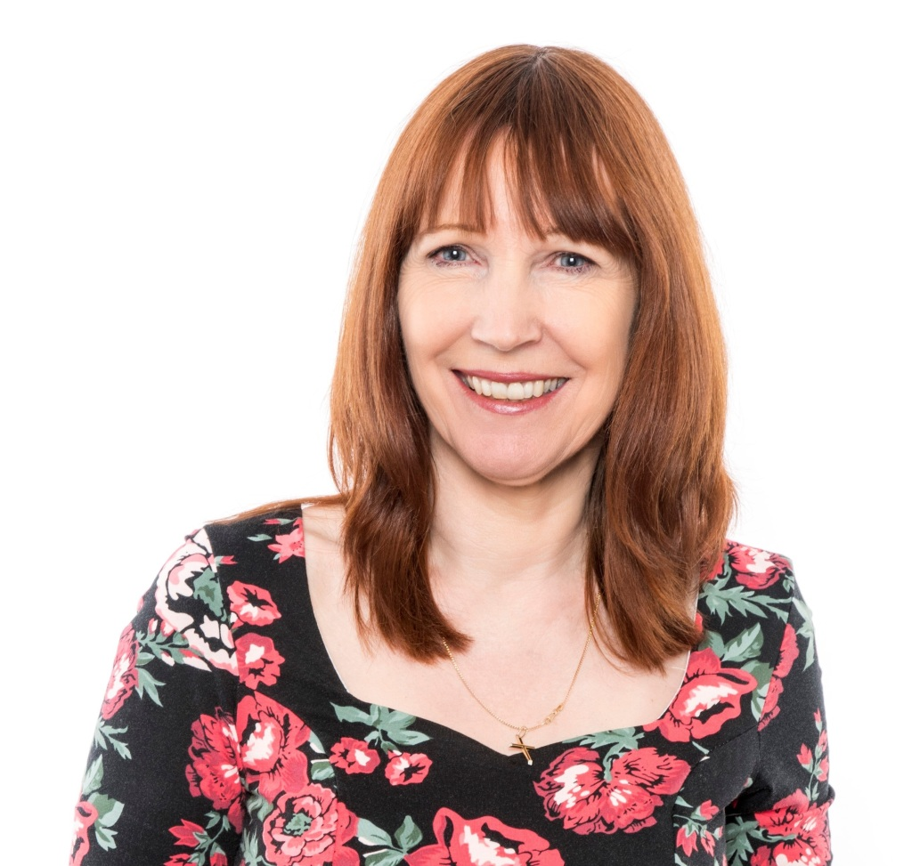 Smiling woman with shoulder length red hair, blue eyes and wearing a floral top